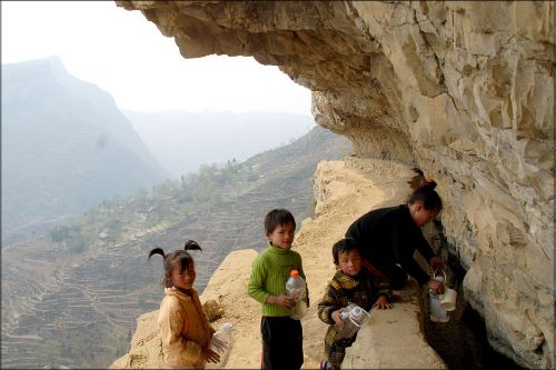 几名彝族女孩在悬崖绝壁上的一条引水渠中汲取生活用水