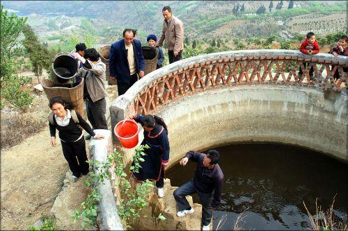 干部群众从即将枯竭的蓄水池取水抗旱