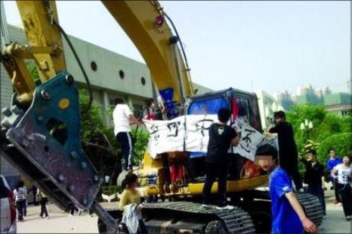 强拆现场 学生将标语挂在拆迁机器上