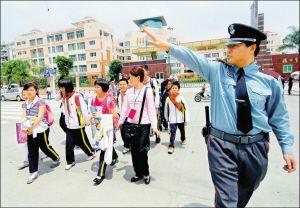 5月4日,专职保安员在引导福州市金山小学学生过街