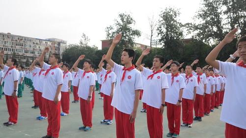 在庄严的国歌声中,初一、初二同学行队礼,全体师生凝视国旗升起